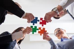 mani che compongono un puzzles