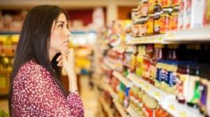 donna davanti a uno scaffale del supermercato