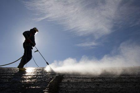 operatore con idropulitrice sul tetto di un edificio