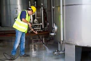 operatore con idropulitrice dentro uno stabilimento