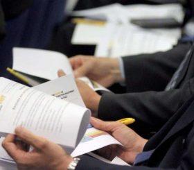 persone a un convegno che sfogliano documenti