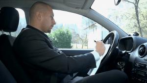 uomo in auto che scrive su un foglio