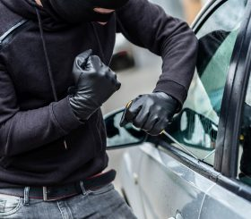 The man dressed in black with a balaclava on his head trying to break into the car. He uses a screwdriver.