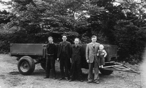 Nella foto da sinistra a destra: nel 1947 a Crakemarsh, Bill Hirst MBE (dipendente numero tre), Arthur Harrison (dipendente numero uno), Bert Holmes (dipendente numero due) e il fondatore della JCB Joseph Cyril Bamford che tiene in braccio un piccolo Lord Bamford