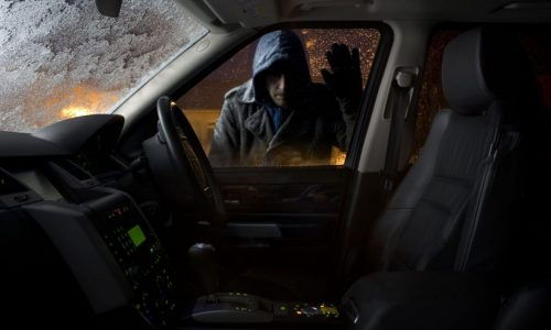 car-thief-looking-into-parked-car-