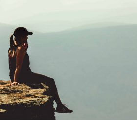 woman-sitting-on-cliff-