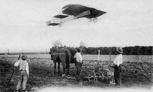 Bleriot monoplane in flight, flying over farmers in a field with a horse drawn plough.