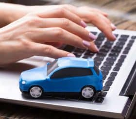 Small BluBusinesswoman Working On Laptop With Small Blue Car